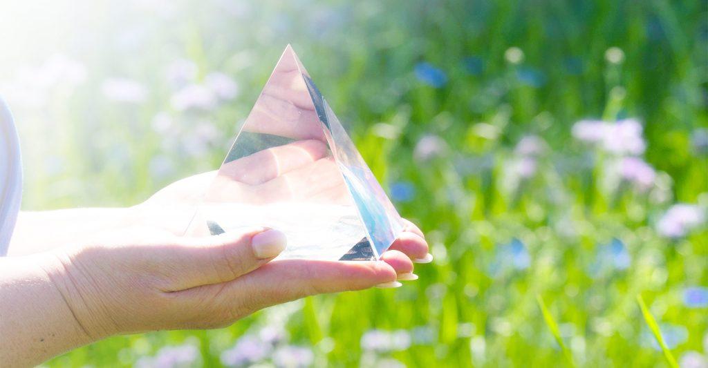 Kristall Pyramide von Händen gehalten